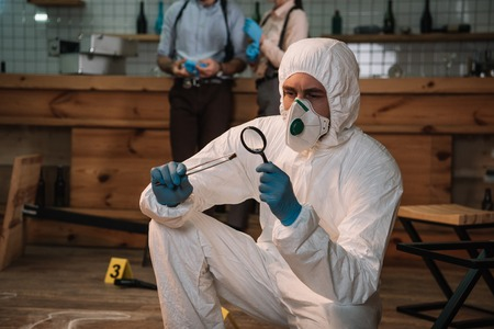 Photo for Focused forensic investigator examining evidence with magnifying glass at crime scene with colleagues working behind - Royalty Free Image
