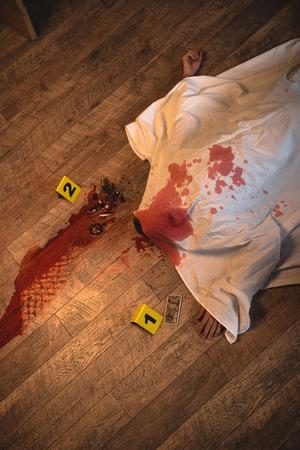 Foto de Top view of dead body covered with white sheet at crime scene - Imagen libre de derechos