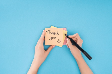 cropped person holding pen above colorful sticky notes with thank you lettering isolated on blue background