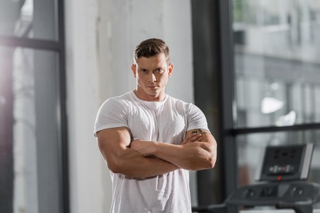 Photo for handsome muscular bodybuilder standing with crossed arms and looking at camera in gym - Royalty Free Image