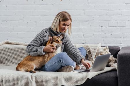 Foto de smiling young blonde woman sitting with welsh corgi dog on sofa and using laptop - Imagen libre de derechos