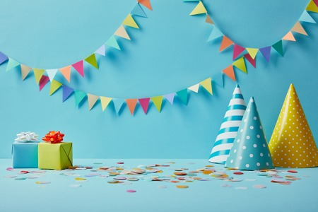Foto de party hats, confetti and gifts on blue background with colorful bunting - Imagen libre de derechos