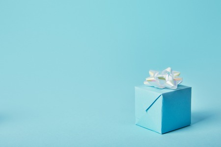 Foto de Gift box with white bow on blue background - Imagen libre de derechos