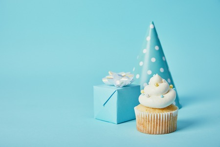 Foto de party hat, gift box and delicious cupcake on blue background - Imagen libre de derechos