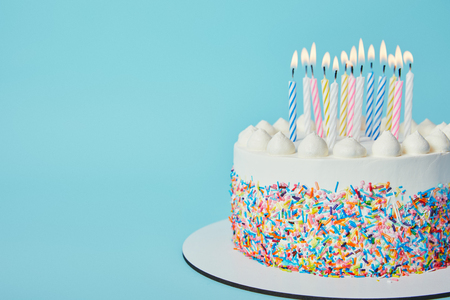 Foto de Delicious Birthday cake with lighting candles on blue background - Imagen libre de derechos