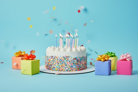 Foto de Tasty cake with candles, colorful gifts and confetti on blue background - Imagen libre de derechos