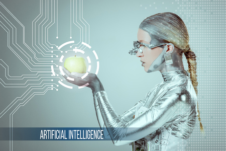 Photo pour side view of cyborg holding and examining green apple with digital data isolated on grey with artificial intelligence lettering - image libre de droit