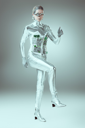 full length view of silver cyborg walking on grey, future technology conceptの写真素材