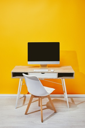 Foto de computer at workplace with chair and yellow wall at background - Imagen libre de derechos