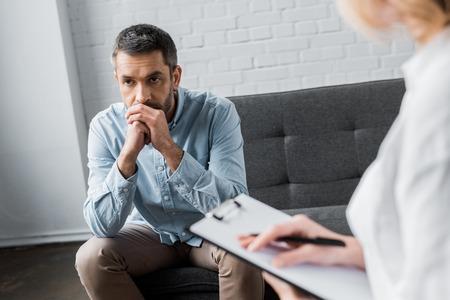 Photo pour depressed adult man on psychologist therapy session at office - image libre de droit