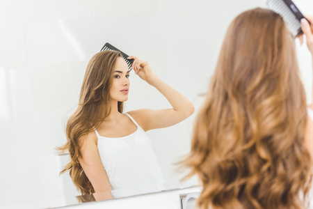 Foto per beautiful woman brushing hair with comb in bathroom - Immagine Royalty Free