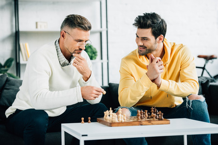 Foto de handsome son and mature father playing chess on weekend at home - Imagen libre de derechos