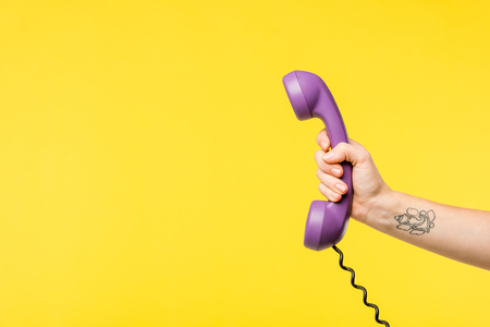 Foto de cropped shot of person holding purple handset isolated on yellow - Imagen libre de derechos
