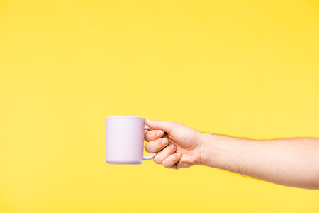 Foto de cropped shot of person holding white cup isolated on yellow - Imagen libre de derechos