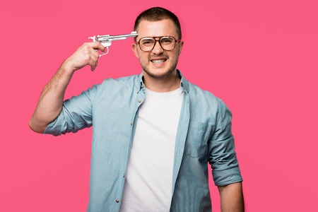 Foto de young man in eyeglasses holding revolver near head and looking at camera isolated on pink - Imagen libre de derechos