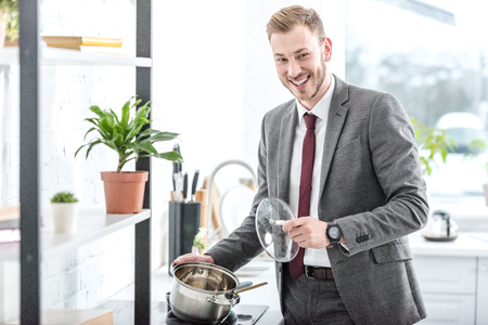 Photo pour Smiling businessman in formal wear holding pot and getting ready to cook in kitchen - image libre de droit