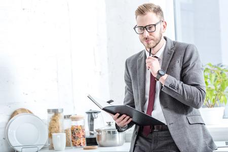 Foto de Pensive businessman holding notebook and pen at kitchen - Imagen libre de derechos
