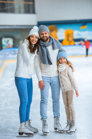 Photo pour Smiling parents and daughter in sweaters looking at camera on skating rink - image libre de droit
