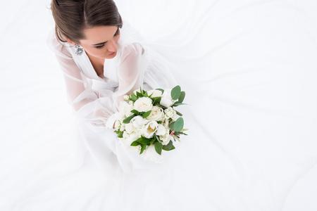 Foto de Overhead view of young bride in dress holding wedding bouquet, isolated on white - Imagen libre de derechos