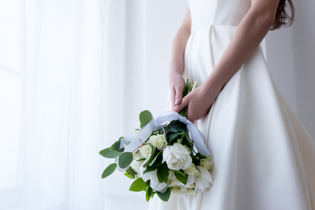 Foto de Cropped view of bride in traditional dress holding wedding bouquet - Imagen libre de derechos
