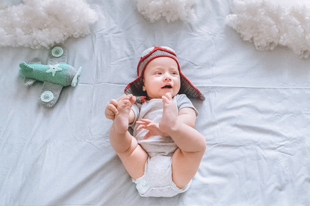 Foto de Top view of dreamy infant child in pilot hat with toy plane surrounded with clouds made of cotton in bed - Imagen libre de derechos