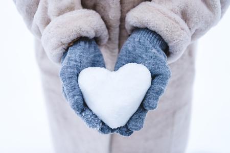 Foto de cropped shot of person holding heart symbol made from snow - Imagen libre de derechos