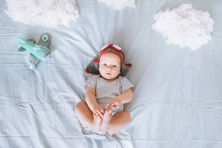 Foto de top view of cute infant child in knitted pilot hat with toy plane surrounded with clouds made of cotton in bed - Imagen libre de derechos