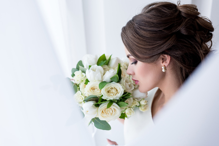 Photo pour attractive brunette bride sniffing wedding bouquet - image libre de droit