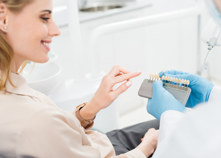 Photo pour Doctor showing tooth implants to female patient in modern dental clinic - image libre de droit
