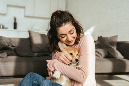 Foto de beautiful woman embracing cute welsh corgi pembroke at home - Imagen libre de derechos