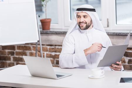 Photo pour Arabian businessman holding folder and pen in office - image libre de droit