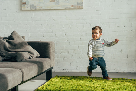 Photo pour happy little boy running in living room at home - image libre de droit