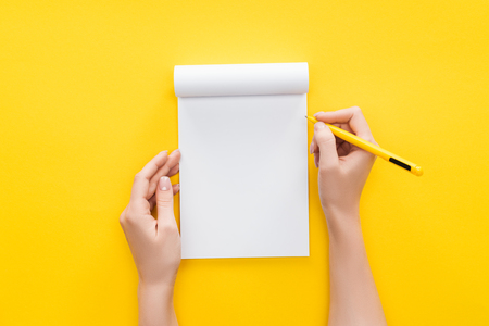Foto de partial view person holding pen over blank notebook on yellow background - Imagen libre de derechos