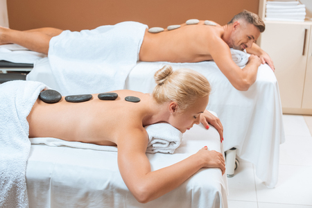 Photo for Couple lying with hot stones on back in spa salon - Royalty Free Image