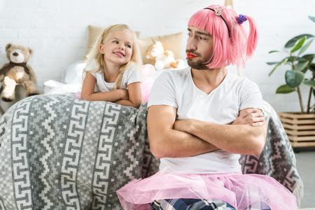 Photo pour adorable happy daughter looking at father in pink wig and tutu skirt - image libre de droit