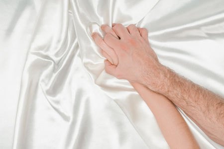 top view of male hand tightly holding female hand on silk white cloth