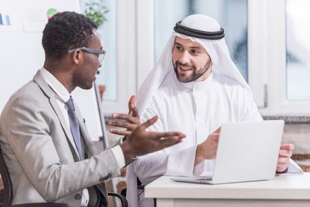 Photo pour Multiethnic businessmen having discussion in modern office - image libre de droit