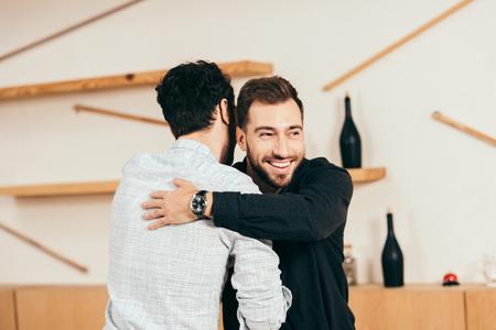 Foto de friends hugging while greeting each other in cafe - Imagen libre de derechos