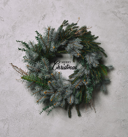 Photo for fir wreath for Christmas decoration hanging on grey wall with merry christmas lettering - Royalty Free Image