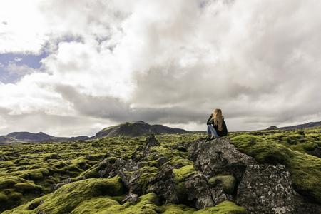 Foto de young woman sitting on rock and looking at majestic icelandic landscape - Imagen libre de derechos
