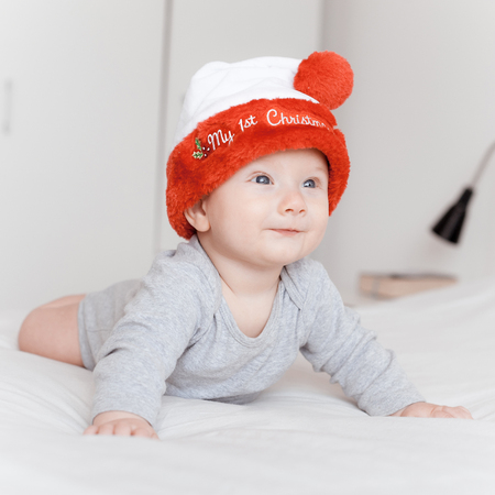 Foto de portrait of beautiful happy infant child in santa hat lying on bed and looking away - Imagen libre de derechos