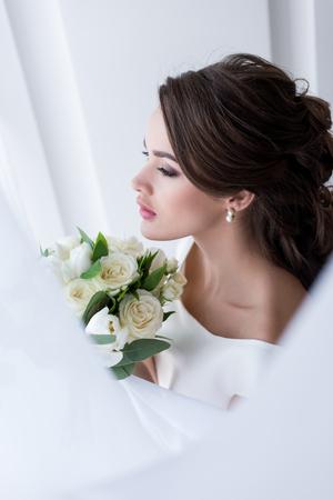 Foto de young brunette bride holding wedding bouquet - Imagen libre de derechos