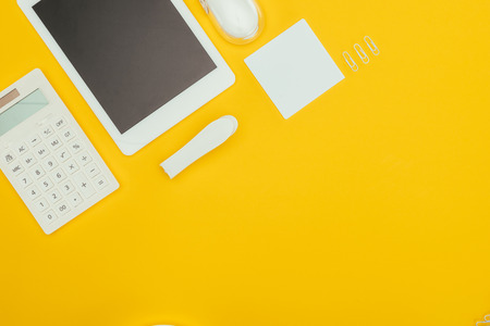 Photo pour top view of digital tablet with blank screen, calculator and office supplies isolated on yellow - image libre de droit