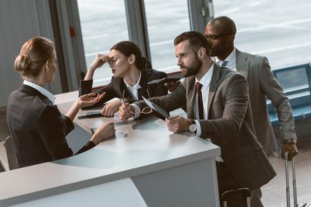 Foto de group of angry businesspeople having argument with airport receptionist - Imagen libre de derechos