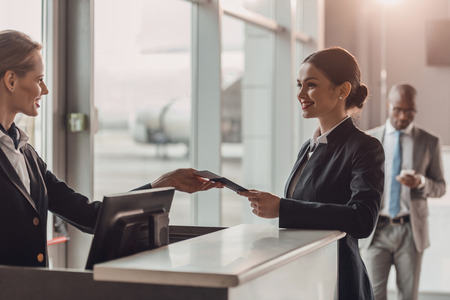 Photo pour smiling young businesswoman giving passport and ticket to staff at airport check in counter - image libre de droit