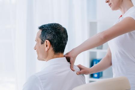 Photo pour masseuse doing seated shoulder massage for businessman - image libre de droit