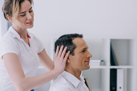 Photo for side view of masseuse doing head massage for handsome mature businessman - Royalty Free Image