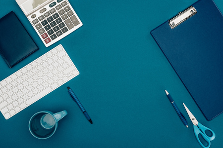 top view of clipboard, calculator and office supplies on blue