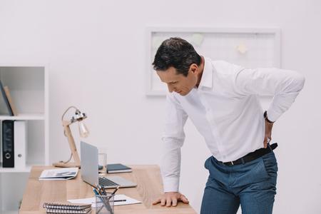 Foto de mature businessman with painful backache at office - Imagen libre de derechos