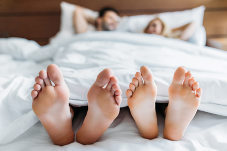 Foto per boyfriend and girlfriend lying in bed with feet on foreground - Immagine Royalty Free